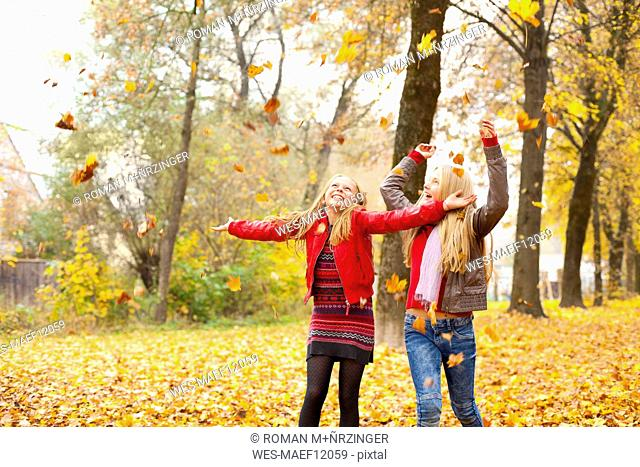 Two happy girls throwing autumn leaves in the air