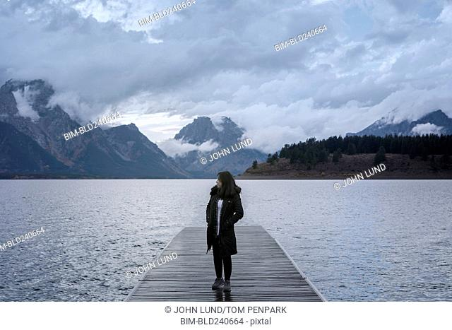 Asian woman standing on dock at lake