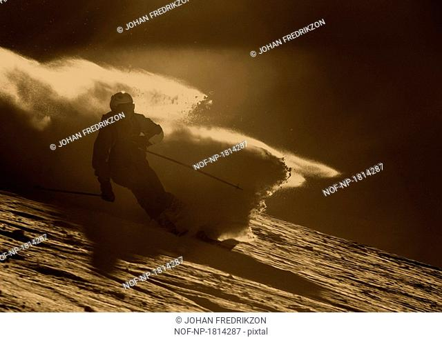 Silhouette of a man downhill skiing
