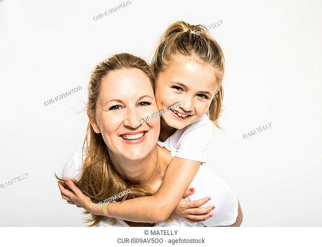 Studio portrait of happy girl getting piggyback from mother