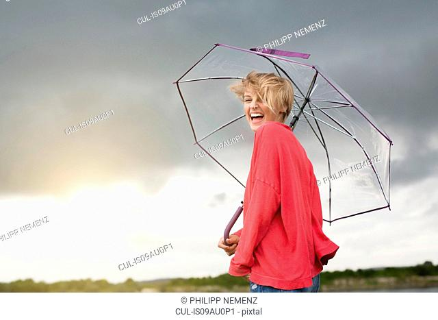 Happy young woman holding transparent umbrella under storm clouds