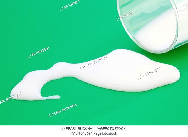 Milk spilt from a glass onto a green surface