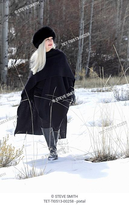 Woman with ushanka walking in snow