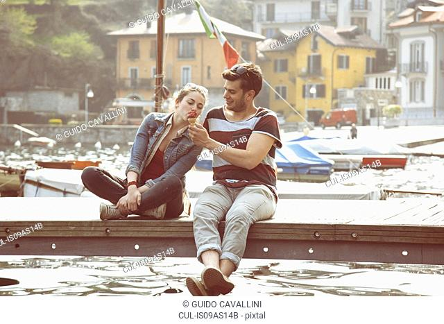 Couple sitting on pier sharing ice cream cone at lake Mergozzo, Verbania, Piemonte, Italy