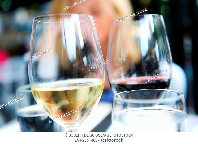 Wine glasses on a table at an outdoor restaurant with a blond woman in the background