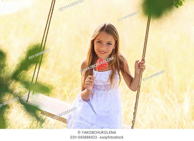Happy childhood. Cute girl is swinging on field and smiling. She is holding candy in shape of heart