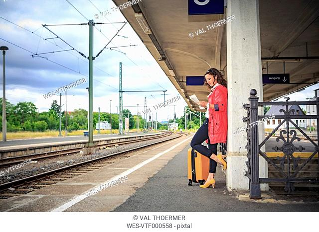 Germany, young woman at rail station in Sonneberg, reading newspaper