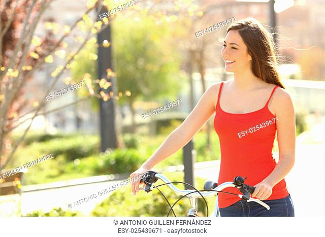 Candid woman walking in an urban park in summer or spring carrying a bicycle
