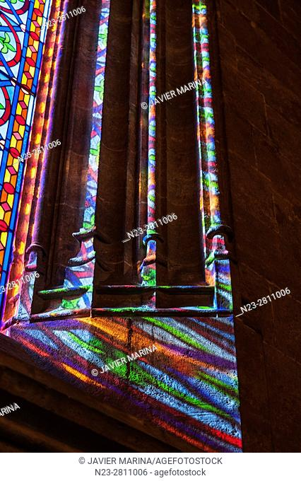 Light from a stained glass window on the side of the window. Building of the Lonja de la Seda (Silk Exchange). Valencia, Spain
