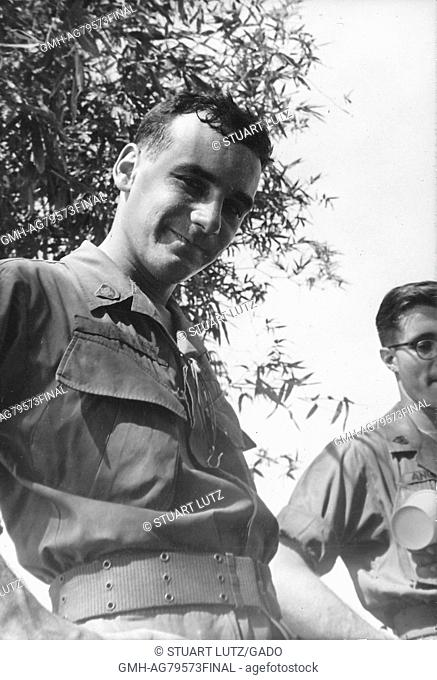 A United States Army serviceman in uniform looking down and smiling, the low vantage point of the camera captures overhead foliage and another soldier, Vietnam