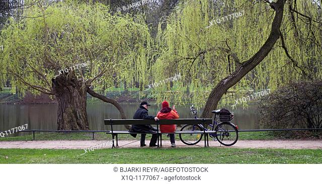 People sitting on a bench at Royal Baths Park, Warsaw Poland
