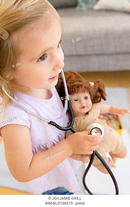 Caucasian girl playing doctor with doll