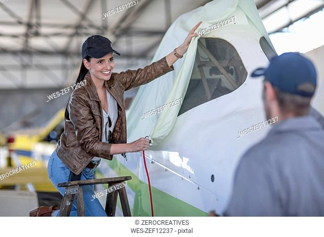 Female pilot and mechanic covering aircraft in hangar