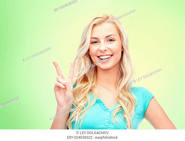 positive gesture and people concept - smiling young woman or teenage girl showing peace hand sign over green natural background