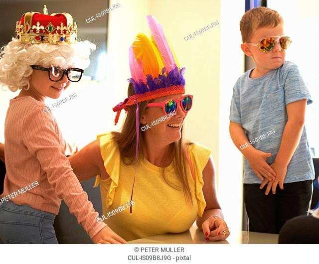 Mother, son and daughter playing dress up, wearing funny hats and glasses, laughing