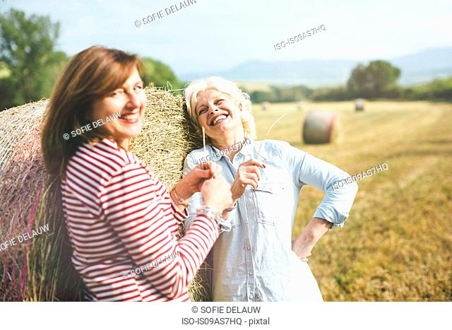 Two mature female friends with straw grass, Tuscany, Italy