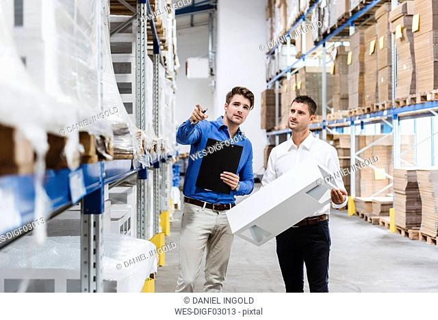 Two businessmen having a meeting in company warehouse
