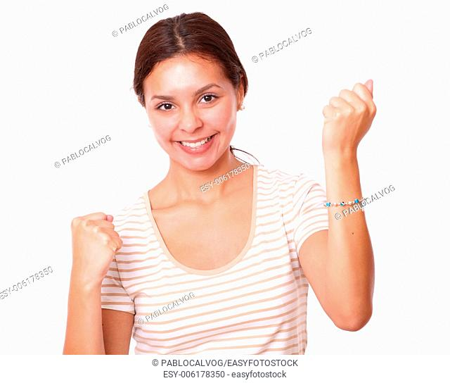 Closeup portrait of lovely latin girl celebrating her victory while smiling at you on isolated studio