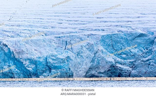 Glacier In Spitsbergen With Turquoise Color And A White Line Of Ice At Sea Level