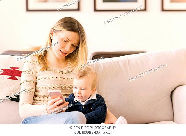 Mother holding baby with smartphone