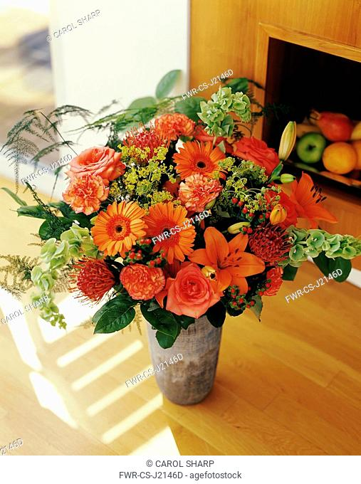 Carnation, Dianthus, Floral arrangment with Gerberas, Oriental Lilies and Bells of Ireland in a vase on a wooden floor