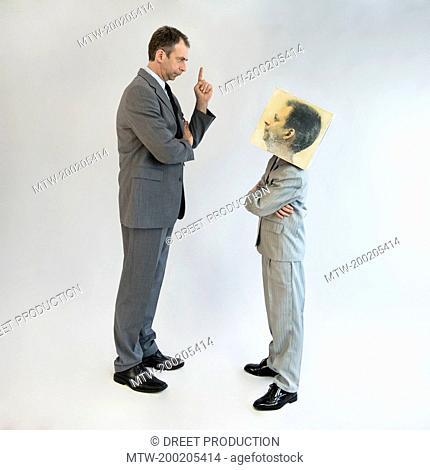 Businessman scolding boy wearing mask