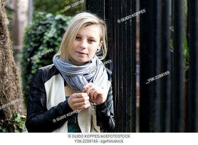 Tilburg, Netherlands. Young, blonde woman leaning against a fence while having a conversation with the photographer