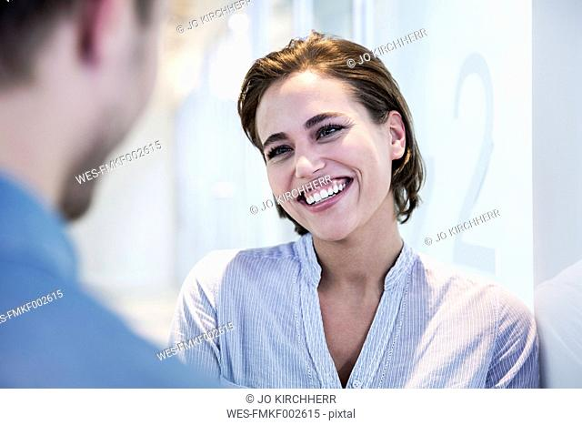 Portrait of smiling woman talking to a man