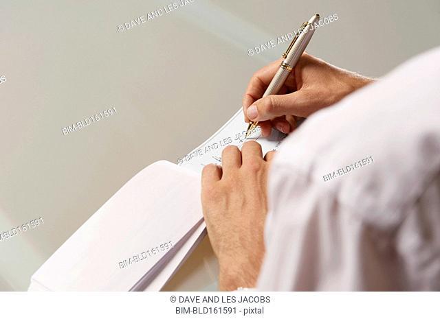 Caucasian businessman writing check