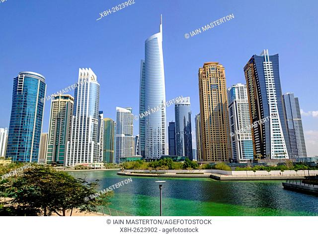 Daytime skyline view of Almas Tower and modern high-rise office and apartment buildings at JLT, Jumeirah Lakes Towers in Dubai United Arab Emirates