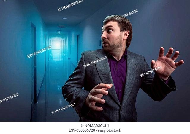 Scared businessman running in the dark corridor