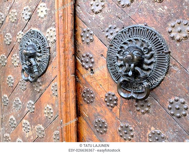 Old wooden door with iron lion knockers. Rustic, vintage