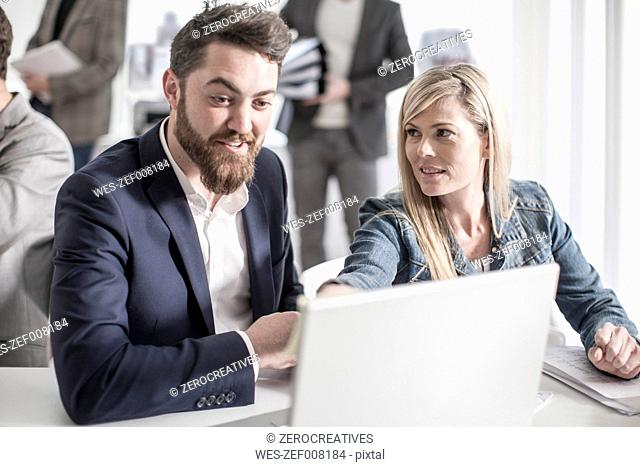 Man and woman in office looking at laptop