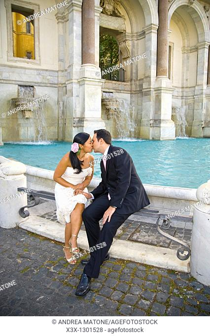 Portrait of newlyweds sitting and kissing in front of Water fountain  Fontanone dell Acqua Paola known as Fontanone del Gianicolo Rome Italy