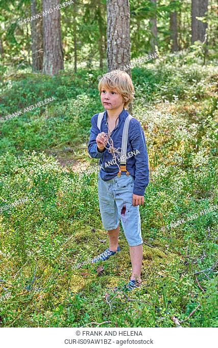 Portrait of young boy wearing retro clothes standing in forest