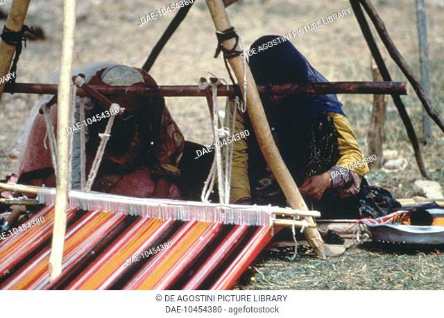 Nomadic Qashqai people weaving a carpet on a horizontal loom, Fars province, Iran