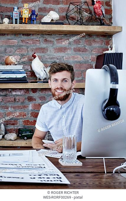 Portrait of creative professional at desk in office