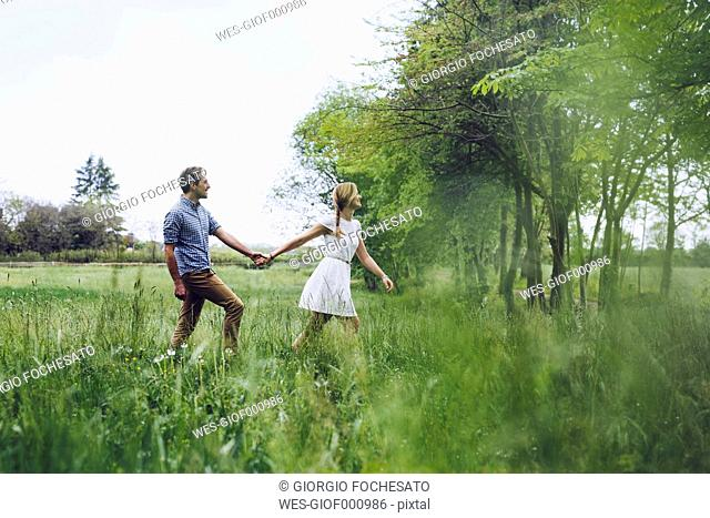 Couple in love holding hands while walking on a meadow