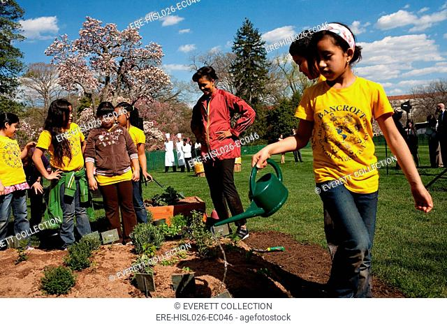 Children from Bancroft Elementary School help First Lady Michelle Obama plant the White House Vegetable Garden April 9 2009