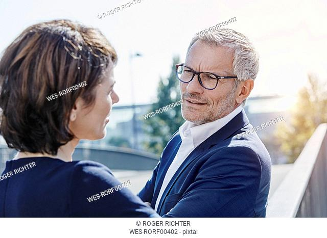 Businessman and businesswoman talking outdoors