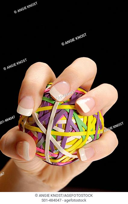 Manicured female had with long fingernails, gripping a rubberband ball as if squeezing or pitching a ball.  Black backround.  Room for text/ copy