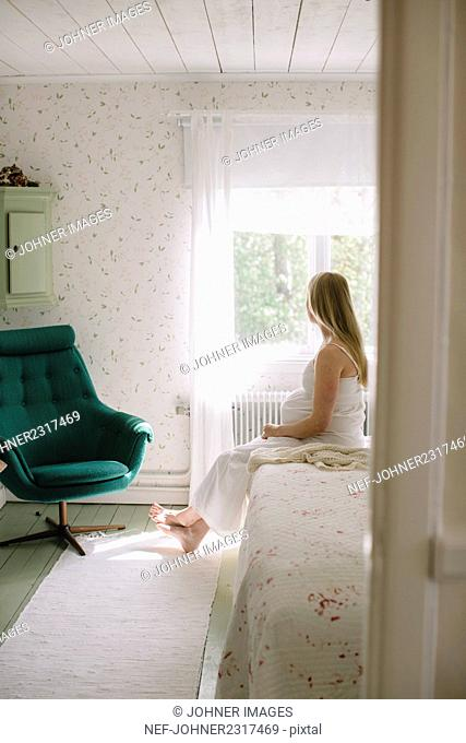 Pregnant woman sitting in bedroom