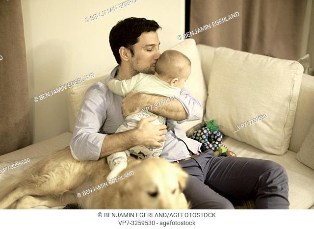 father with baby and dog at couch at home, in Munich, Germany