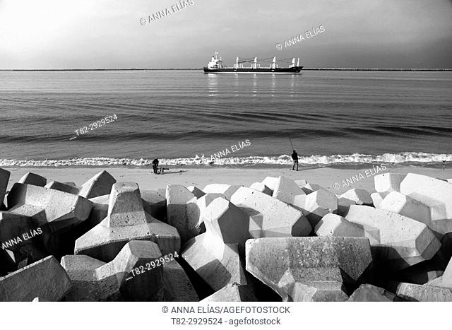Two fishermen on the beach with cargo ship on background and boundary stones on foreground. Mazagon, Huelva province, Andalusia, Spain