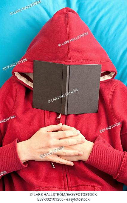 Woman wearing hoodie lying down with a book covering her face