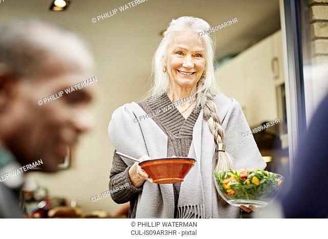 Senior woman carrying bowls of salad outside