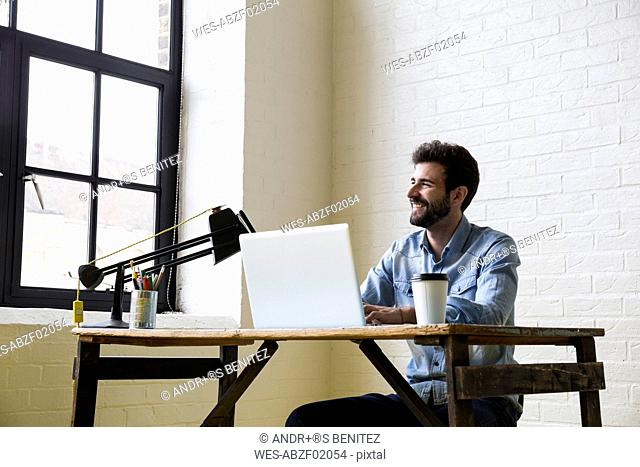 Smiling man sitting at desk working with his laptop