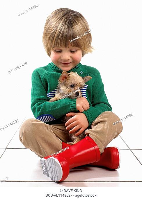 Boy (3 years) hugging puppy