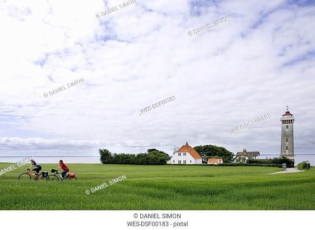 Denmark, Fuenen, Couple mountain biking across farm track, lighthouse in background
