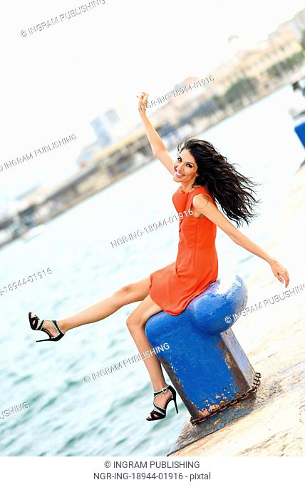 Brunette woman, model of fashion, wearing orange short dress happy in an urban harbor. Young girl with curly hairstyle happy in the beach